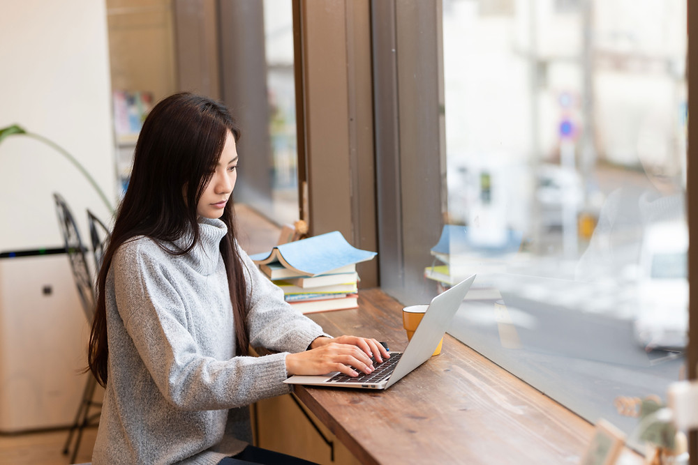 woman typing on her laptop on a desk by a window