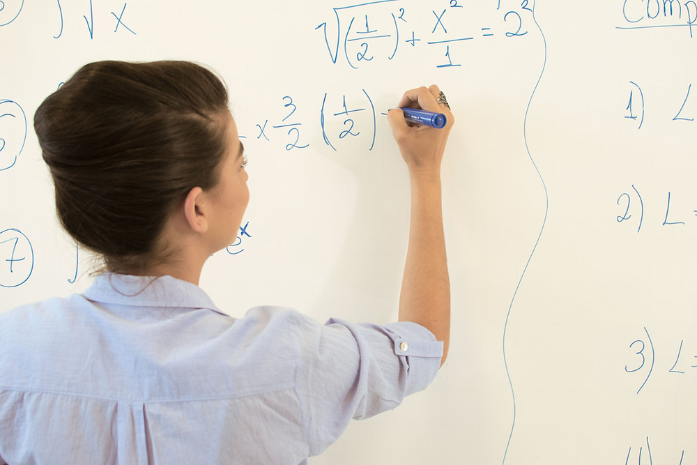 A young female teacher writes mathematic equations on a whiteboard