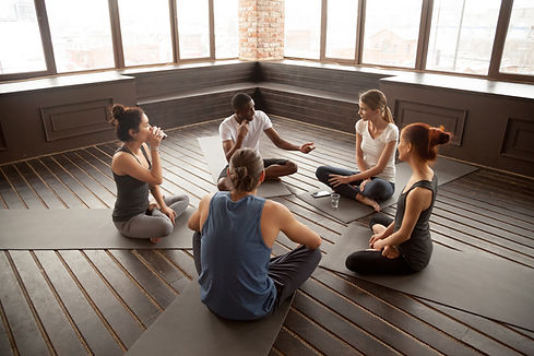 Young man guiding a yoga and breathing technique and afterclass discussion