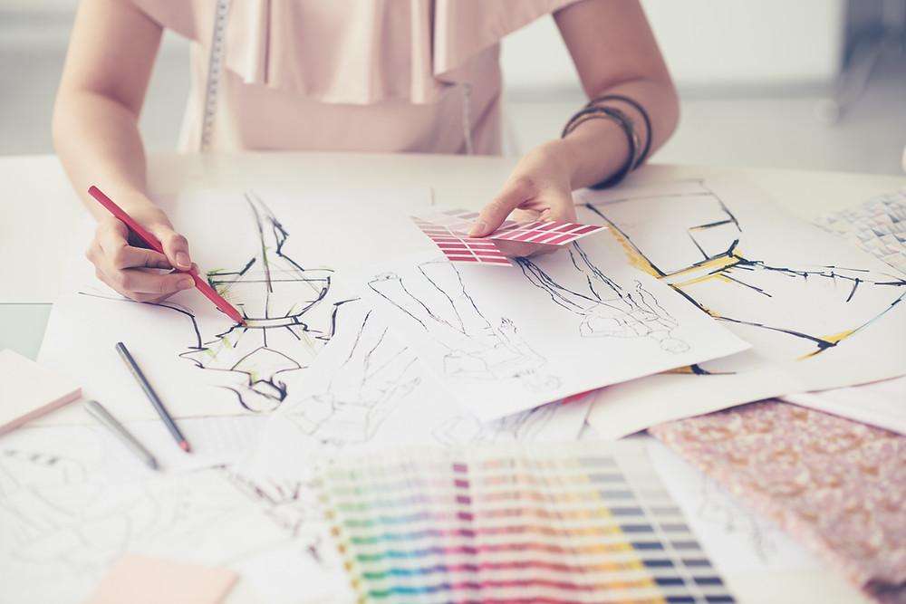 A female fashion designer sketching clothing designs on paper