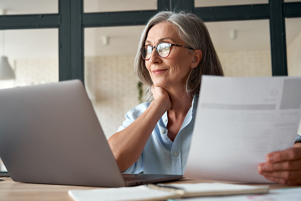A lady holding some paperwork while looking at a computer s screen.