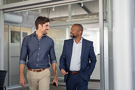 Two male colleagues walking and having a conversation.
