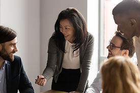 Woman standing over a work desk and talking with colleagues.