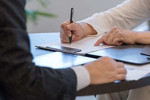 シニアイメージ 書類にサインをするシニア女性