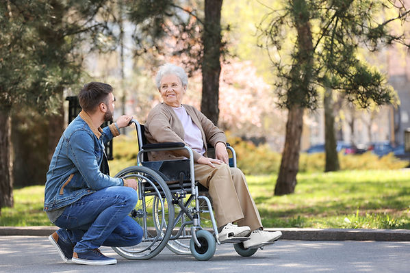 A senior lady is seated in a wheelchair outside on a walkway. She is wearing a beige outfit and white runners. Kneeling beside her wheelchair in the foreground is a young male in a blue jean outfit, he is facing the lady and they are both smiling. Trees and green grass are in the background.