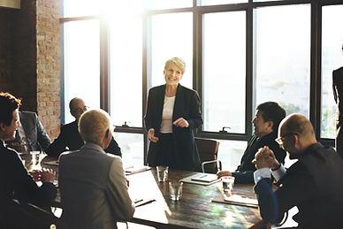 Femme d'age mûre en pleine présentation lors d'un réunion. Elle est ses collaborateurs ont l'air confiants et détendus. On s'ent un excellent climat de travail. Image acollée à une texte ui parle des bienfants de la pratique de la sophrologie en entreprise.