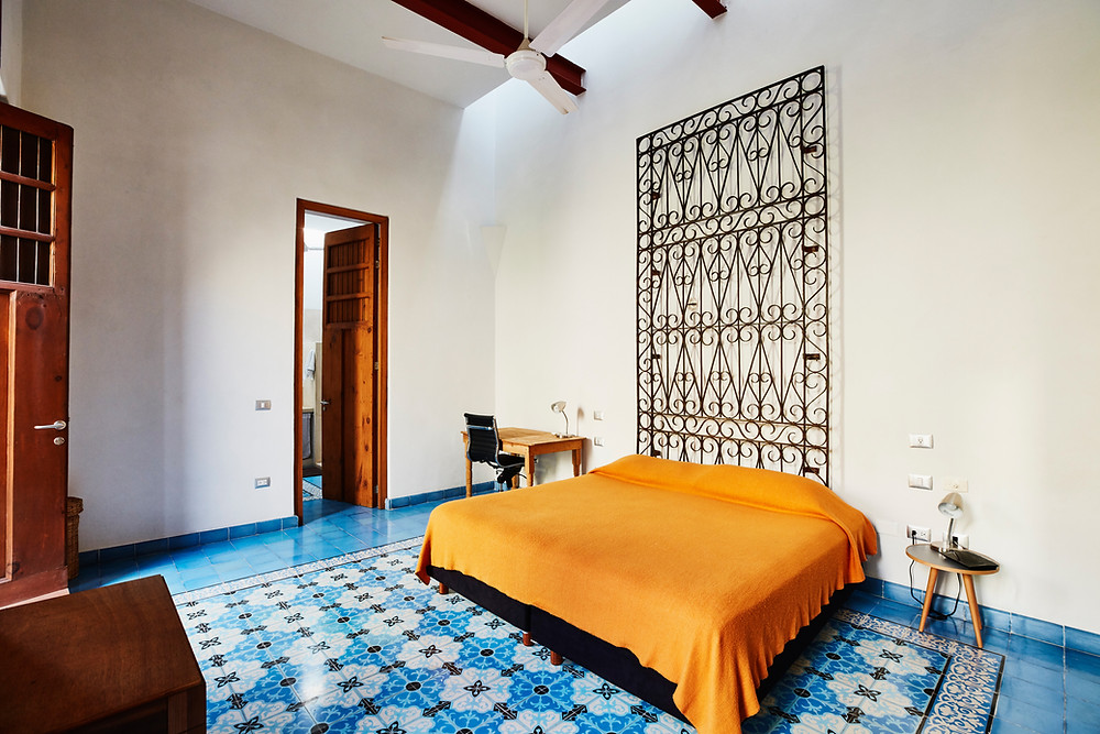 Iron on the wall and orange color on the bed. Warm and original.