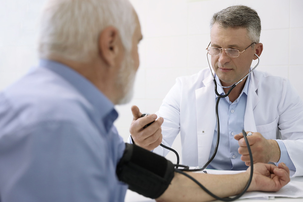 Medical professional in a white labcoat with a stethoscope checking blood pressure of another man with a blood pressure cuff on his arm.