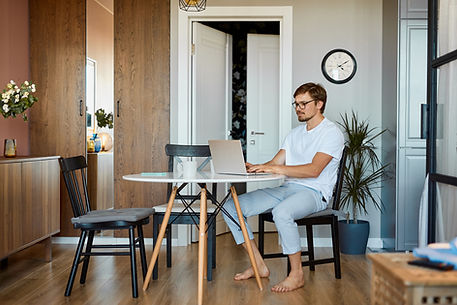 A male in his 30s with glasses and a short beard is seated in a kitchen chair, and working on a laptop on a small round kitchen table. His bare feet are supported on the wood floor, he is slouched slightly in the chair. He is wearing a white T-shirt, both hands are on the laptop keyboard. A clock is on the grey wall behind him and beside a white open door. A green palm plant is behind him.
