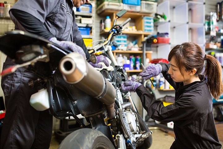 Mujer arreglando una motocicleta