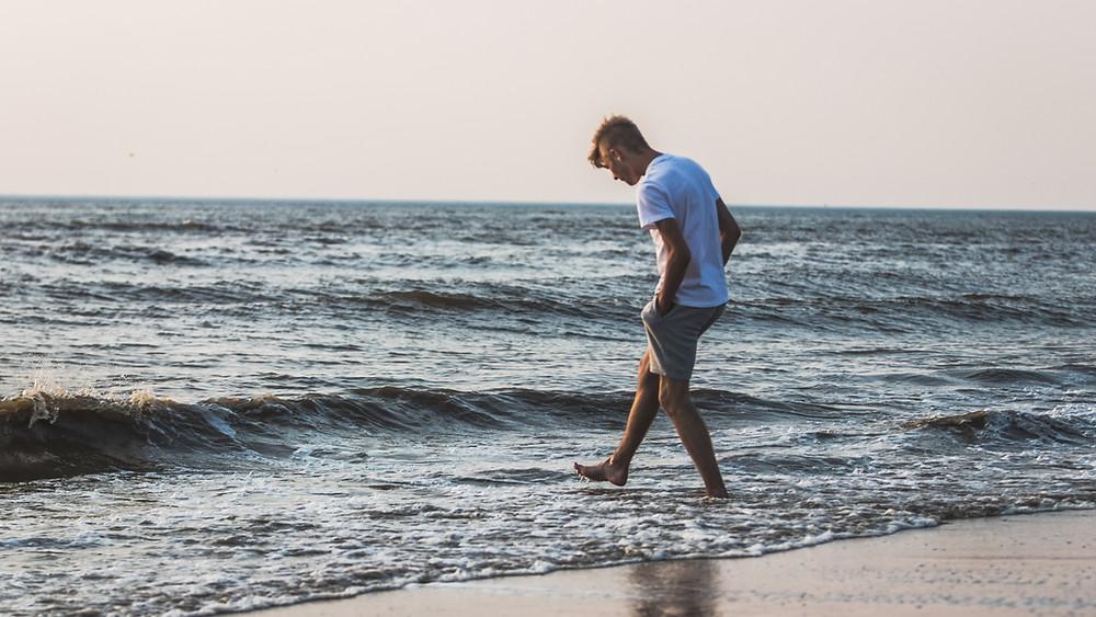 Man dipping feet in the ocean surf