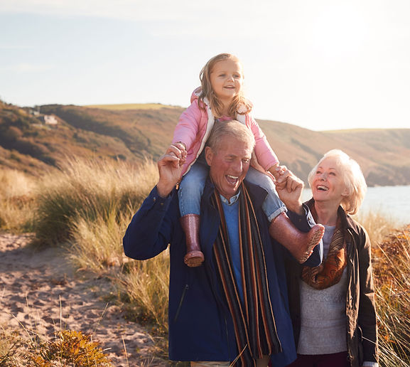 Grandparents taking a walk with their granddaughter on a sunny day