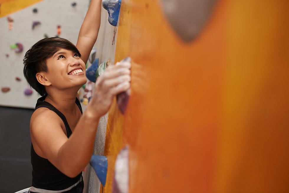 A Woman Climbing a Wall