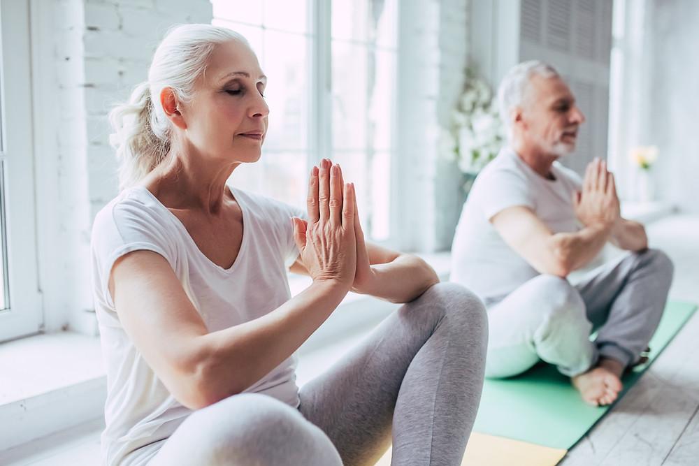 older white man and woman meditating