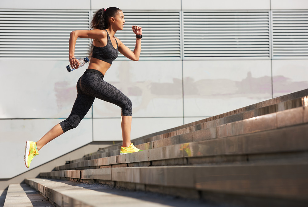 On a hot day, an athlete is vigorously running up many steps to reach her goal at the top.