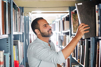 Man taking book off shelf