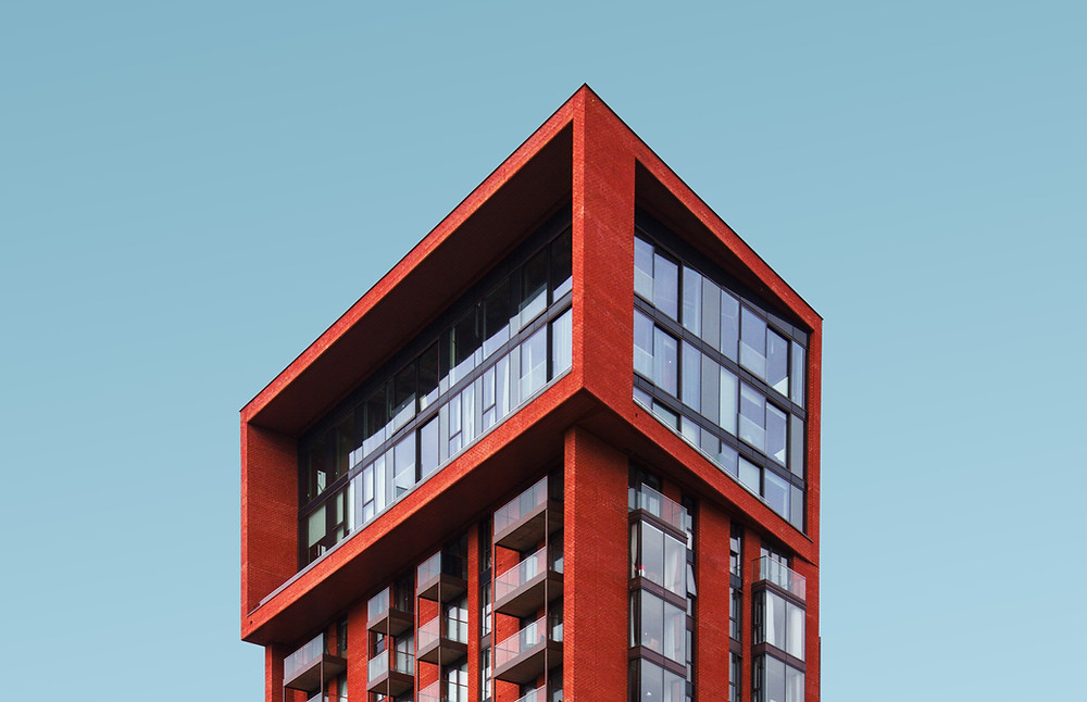 Picture of tall red building with glass windows, high up in the sky.
