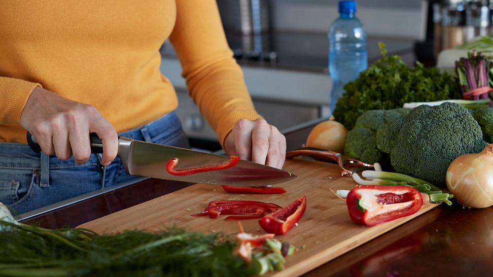 Woman slicing red bell pepper