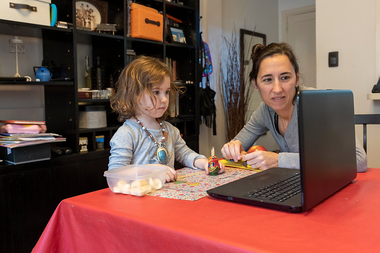 Child at home with mother looking at laptop together.
