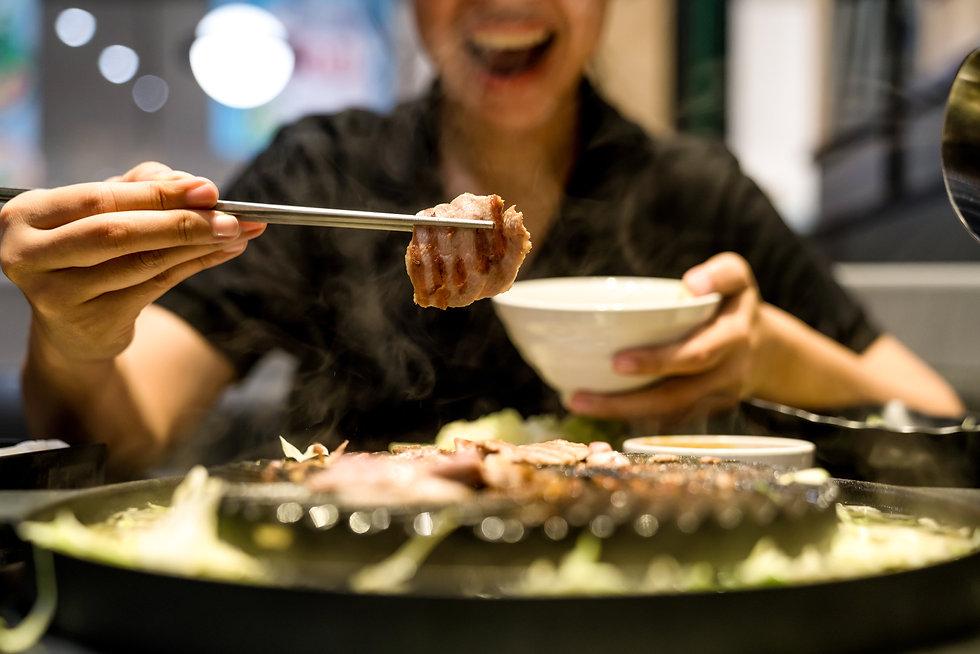 Chopsticks Grabbing Piece Of Grilled Pork
