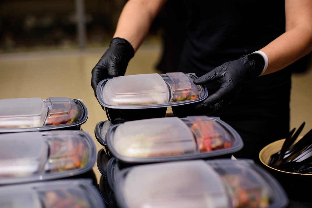 a worker piling up to-go containers of meals