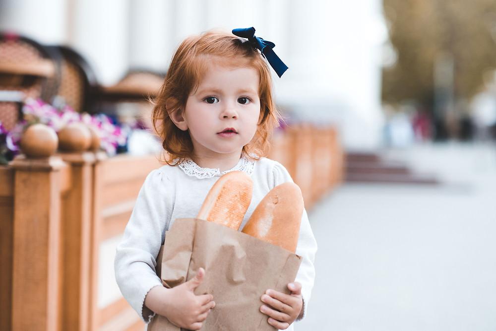 Inviter l'enfant et une petite fille à rentrer dans la vie pratique en la laissant porter le pain
