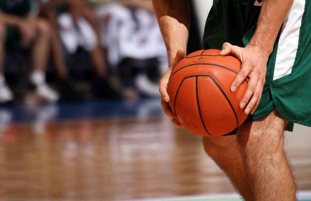 A man in green shorts holding a basketball during a basketball game
