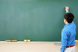 黒板に向かう教師