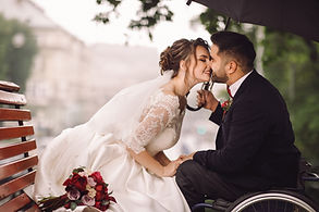 A happy newly wed couple are kissing. She is in her white wedding dress and seated on a wooden outdoor bench. He is leaning foward in his tuxedo and holding onto an umbrella, while they kiss. He is using a wheelchair.