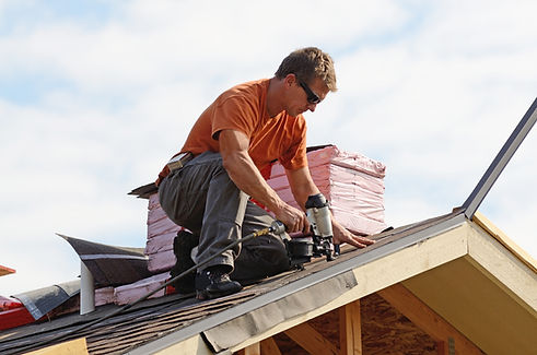 Man in orange shirt installing roofing shingles with nail gun