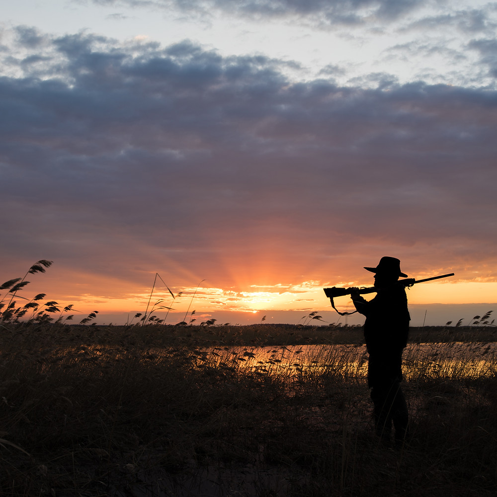 A man with a rifle over his shoulder in silhouette at sunruse