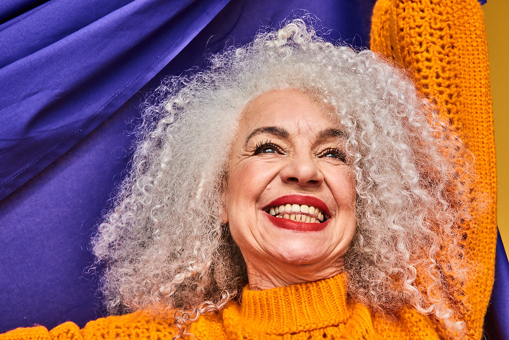 A Stylish Silver Haired Woman Wearing Orange