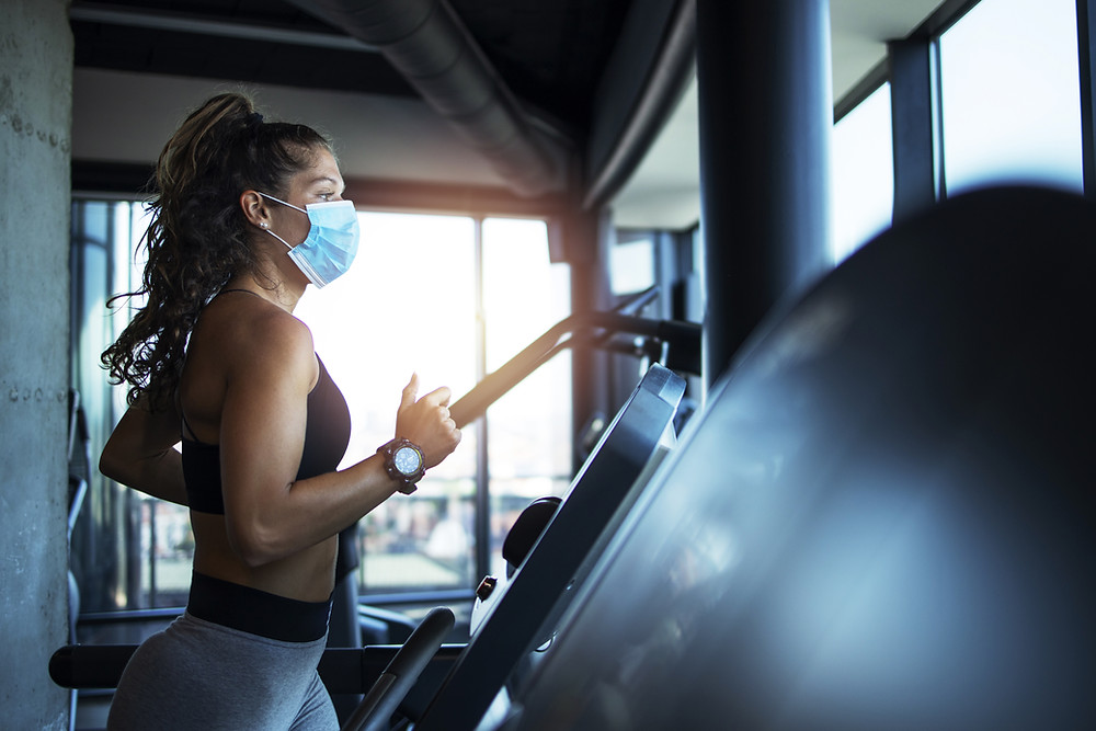 Lady exercising using a mask in a safe Covid gym environmental