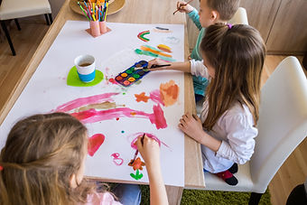 young children painting on a table