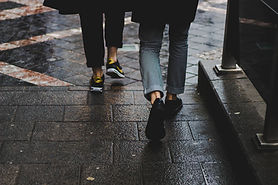 Photo of two people's shoes as they walk along the pavement