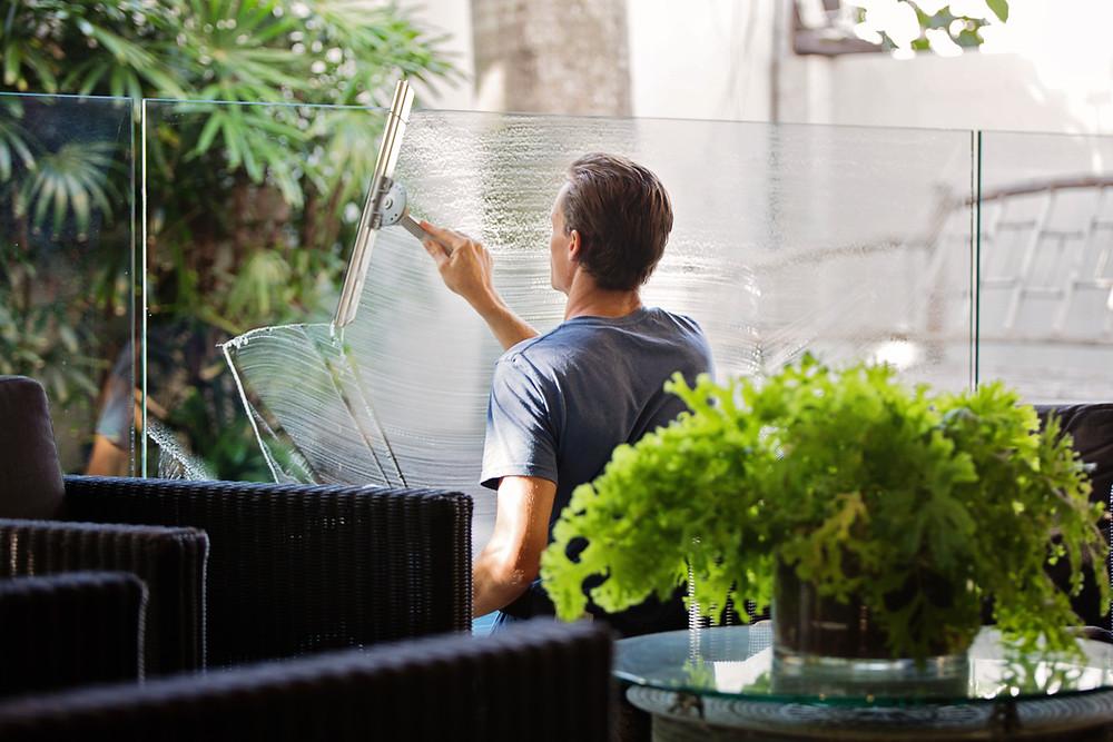 Mann putzt Fenster