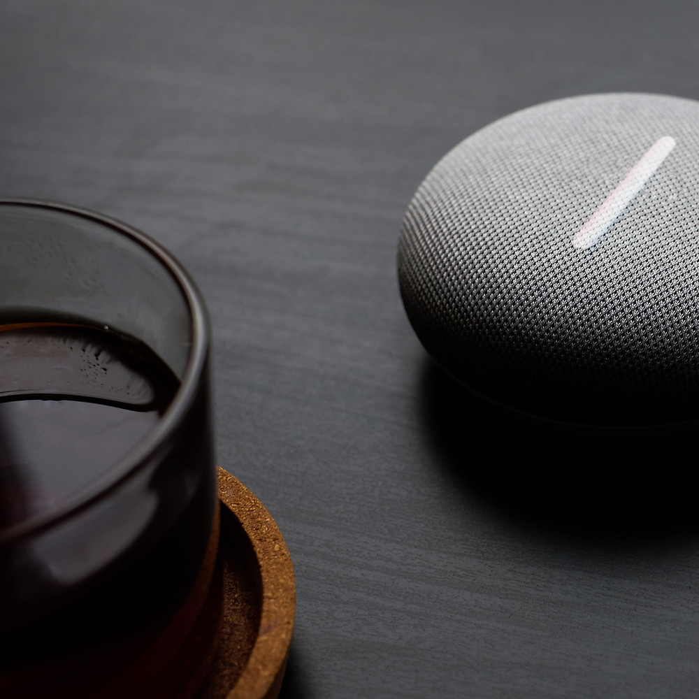 A grey smart speaker on a table
