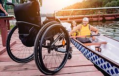 Male and female in a boat smiling with a wheelchair left behind on the dock