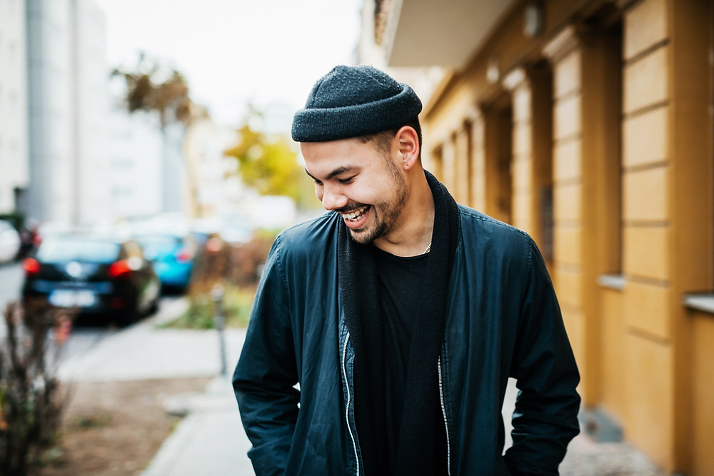 a laughing man in a black monochromatic outfit
