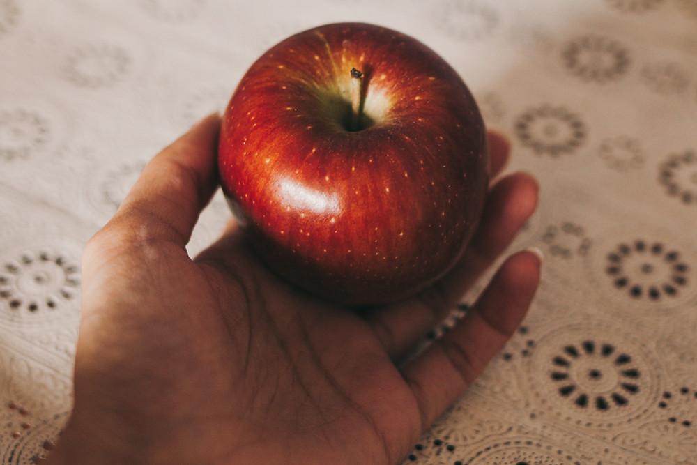 Mão segurando maçã