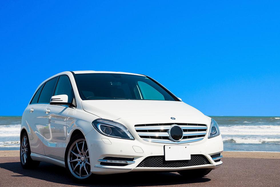 真夏のドライブイメージ (白い車と海と青空)