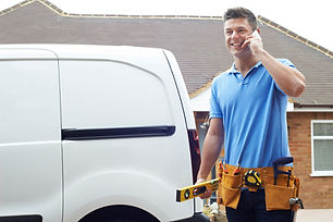 Ein freundlicher Handwerker mit Werkzeuggürtel vor seinem Dienstwagen telefoniert. Die Baugenossenschaft Gartenstadt Luginsland eG bietet exzellenten Service bei Schäden.