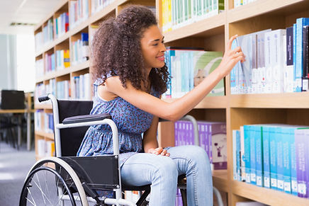 Smiling African American girl in a wheelchair visiting a library