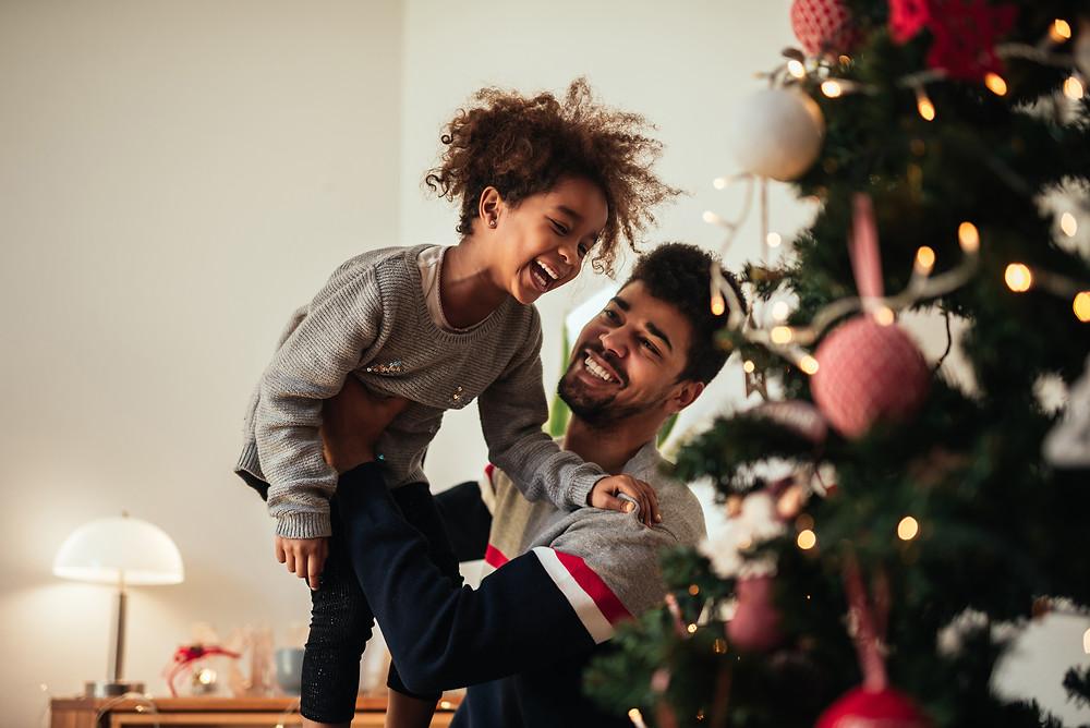 Fillette riante, soulevée par son papa devant un sapin de Noël