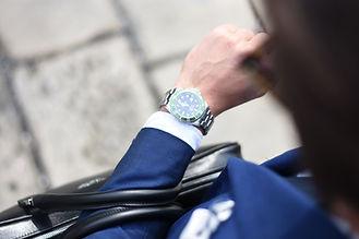 彼の時計をチェックする男
