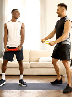 2 men standing in a room smiling holding on to resistance bands