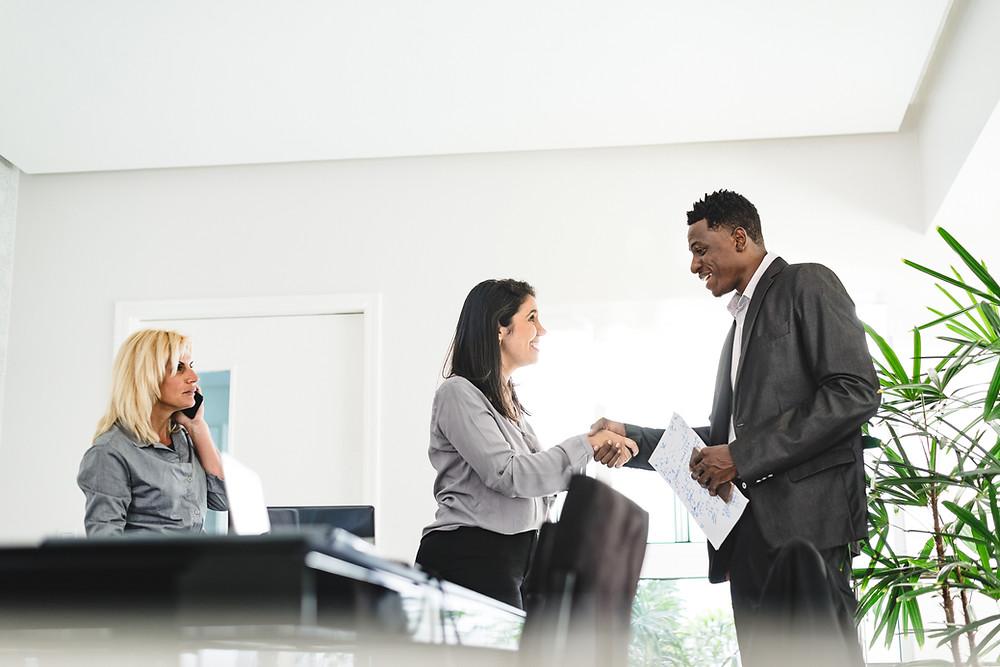 mulher se apresentando a um homem em um ambiente de trabalho