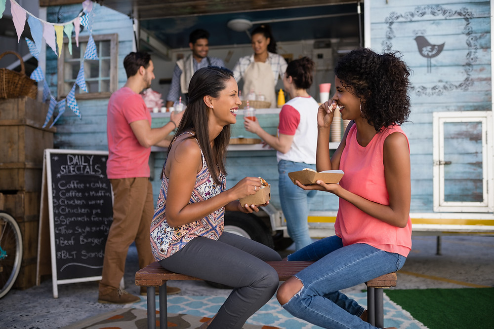two friends eating in front of food stall