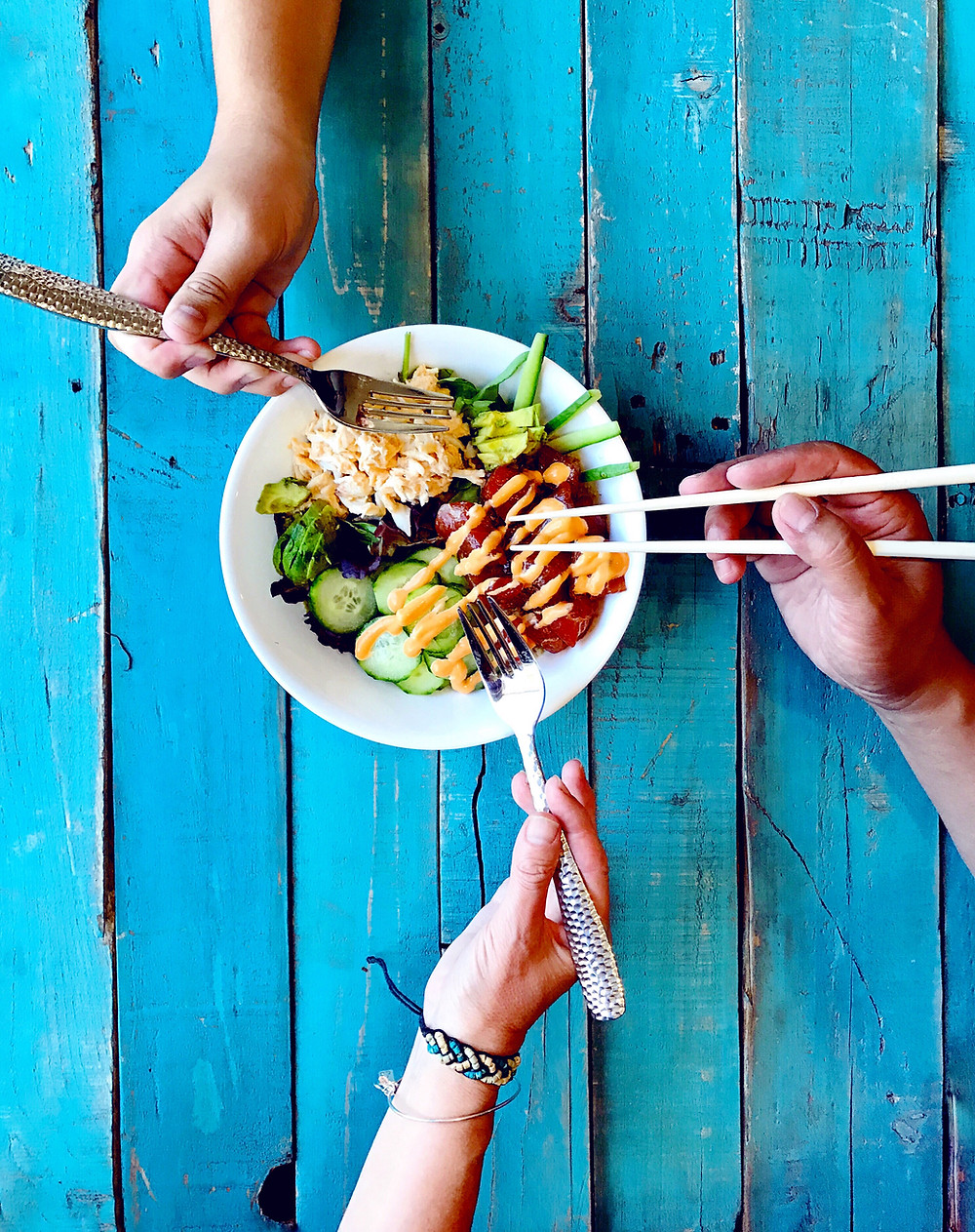 3 hands using chopsticks to eat from a bowl