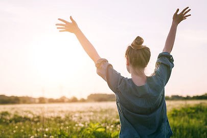 Woman facing the sun with arms stretched out above head, triumphant that she has conquered her pelvic floor problems